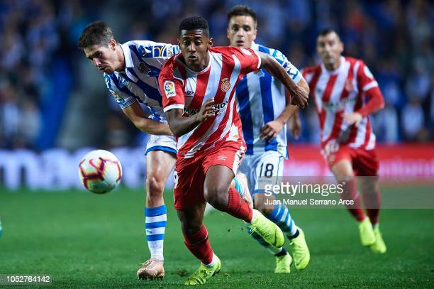 Anthony Lozano of Girona FC being followed by Aritz Elustondo of Real Sociedad during the La Liga match between Real Sociedad and Girona FC at...
