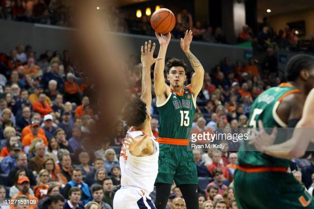 Anthony Mack of the Miami Hurricanes shoots over Marco Anthony of the Virginia Cavaliers in the first half during a game at John Paul Jones Arena on...