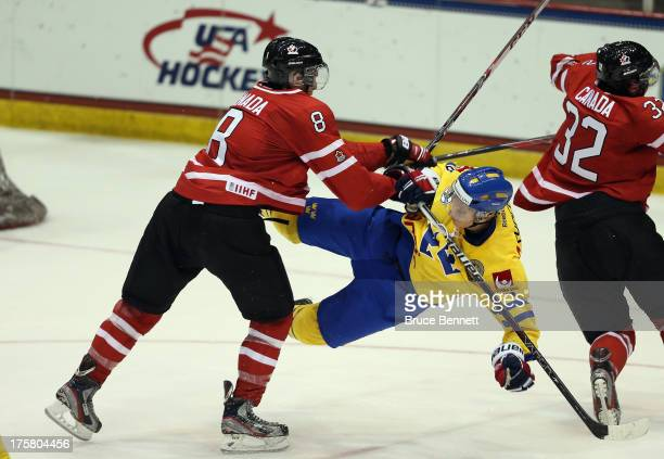 Anthony Mantha of Team Canada checks Andre Burakowsky of Team Sweden during the 2013 USA Hockey Junior Evaluation Camp at the Lake Placid Olympic...