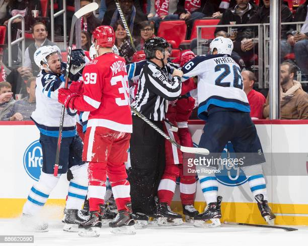 Anthony Mantha of the Detroit Red Wings and Josh Morrissey of the Winnipeg Jets battle after a stoppage in play along with other teammates during an...