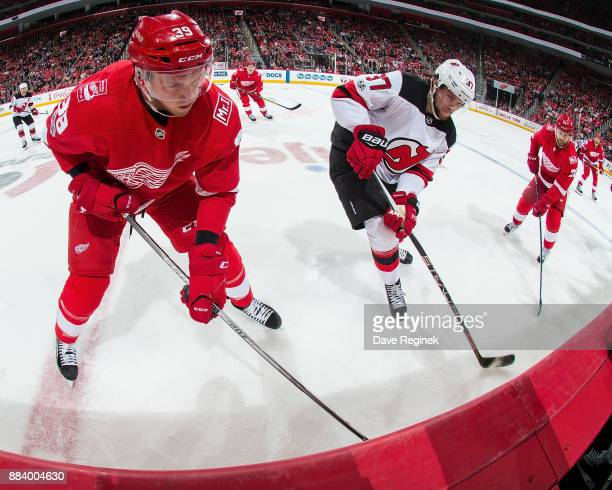 Anthony Mantha of the Detroit Red Wings battles along the boards with Pavel Zacha of the New Jersey Devils during an NHL game at Little Caesars Arena...