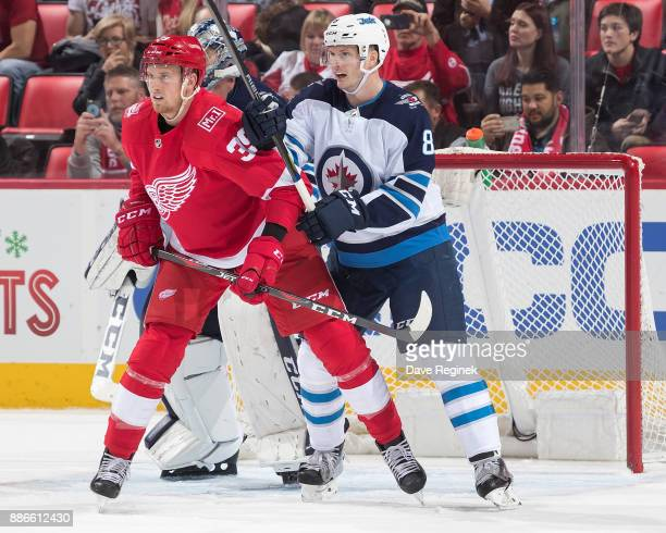 Anthony Mantha of the Detroit Red Wings battles for position with Jacob Trouba of the Winnipeg Jets in front of goaltender Connor Hellebuyck of the...