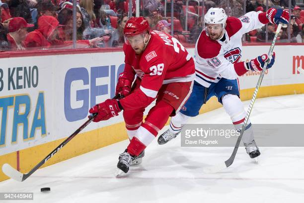 Anthony Mantha of the Detroit Red Wings battles for the puck behind the net with Logan Shaw of the Montreal Canadiens during an NHL game at Little...