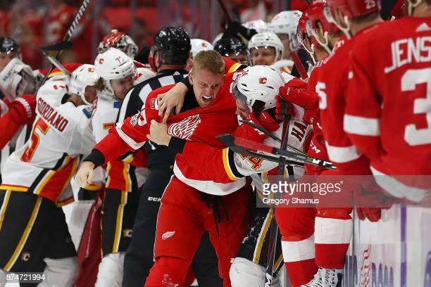 Anthony Mantha of the Detroit Red Wings gets in a fight with Travis Hamonic of the Calgary Flames during the third period at Little Caesars Arena on...