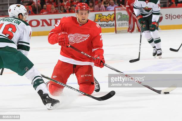 Anthony Mantha of the Detroit Red Wings plays the puck in front of Jared Spurgeon of the Minnesota Wild during the first ever NHL game at the new...