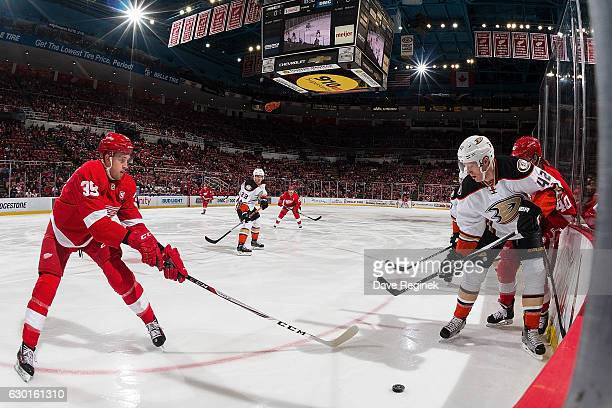 Anthony Mantha of the Detroit Red Wings pokes the puck away from Josh Manson of the Anaheim Ducks during an NHL game at Joe Louis Arena on December...