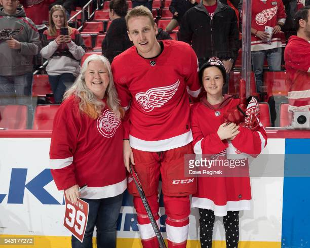 Anthony Mantha of the Detroit Red Wings poses with season ticket holders following an NHL game against the New York Islanders at Little Caesars Arena...
