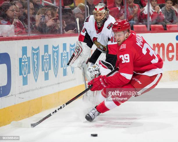 Anthony Mantha of the Detroit Red Wings reaches for the puck as goaltender Craig Anderson of the Ottawa Senators clears it behind the net during an...