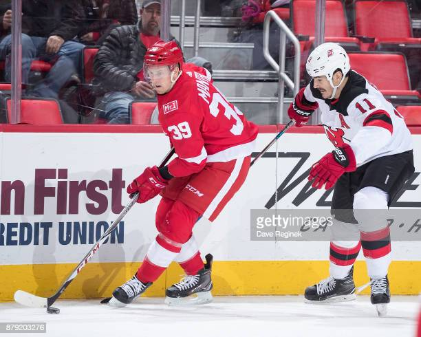 Anthony Mantha of the Detroit Red Wings skates along the boards with the puck followed by Brian Boyle of the New Jersey Devils during an NHL game at...