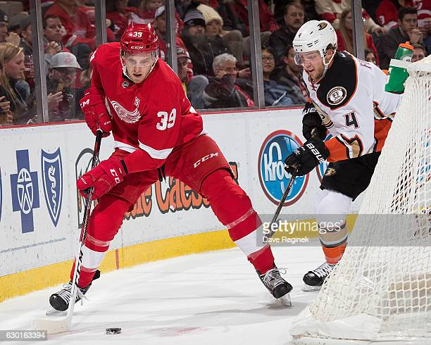 Anthony Mantha of the Detroit Red Wings skates with the puck as Cam Fowler of the Anaheim Ducks pressures him behind the net during an NHL game at...