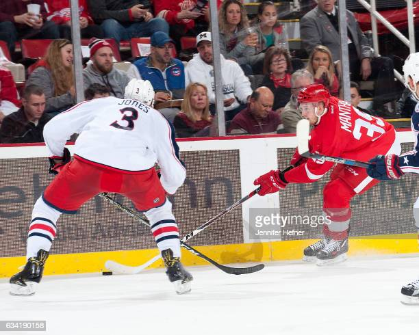 Anthony Mantha of the Detroit Red Wings skates with the puck as Seth Jones of the Columbus Blue Jackets pressures him during an NHL game at Joe Louis...
