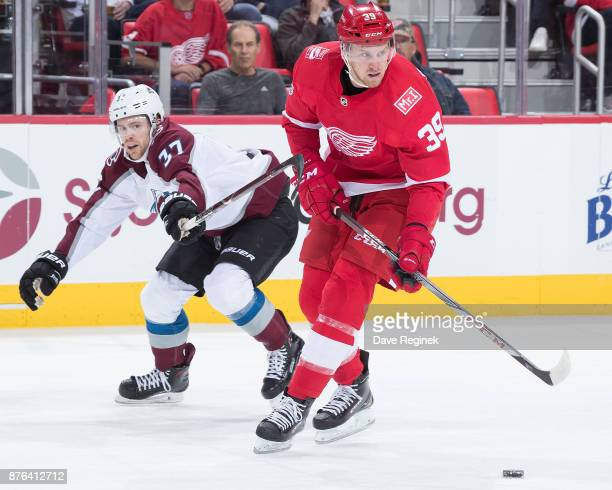 Anthony Mantha of the Detroit Red Wings skates with the puck in front of JT Compher of the Colorado Avalanche during an NHL game at Little Caesars...