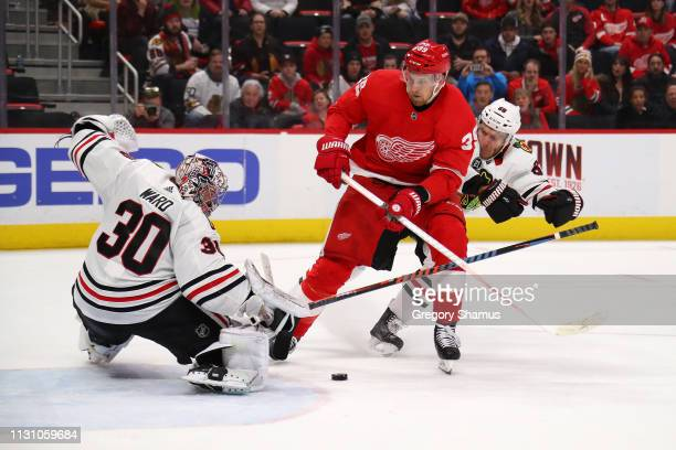 Anthony Mantha of the Detroit Red Wings tries to get a shot off between Cam Ward and Slater Koekkoek of the Chicago Blackhawks during overtime at...