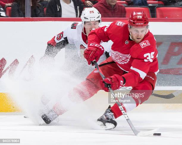 Anthony Mantha of the Detroit Red Wings turns up ice with the puck followed by Matt Duchene of the Ottawa Senators during an NHL game at Little...