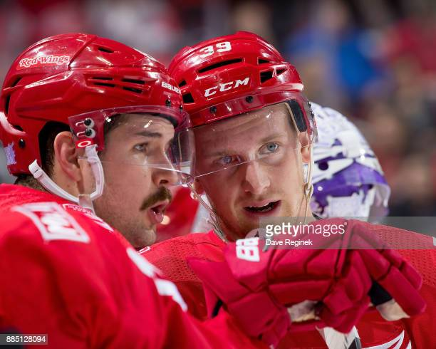 Anthony Mantha talks with Xavier Ouellet of the Detroit Red Wings before a face off during an NHL game at Little Caesars Arena on November 28 2017 in...