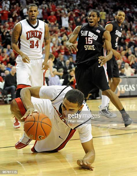 Anthony Marshall of the UNLV Rebels comes up with a loose ball in front of teammate Matt Shaw and Kawhi Leonard of the San Diego State Aztecs during...
