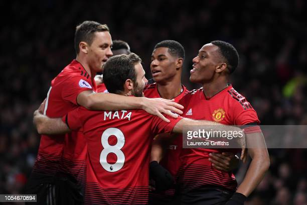Anthony Martial celebrates with teammates Nemanja Matic and Juan Mata after scoring his team's second goal during the Premier League match between...