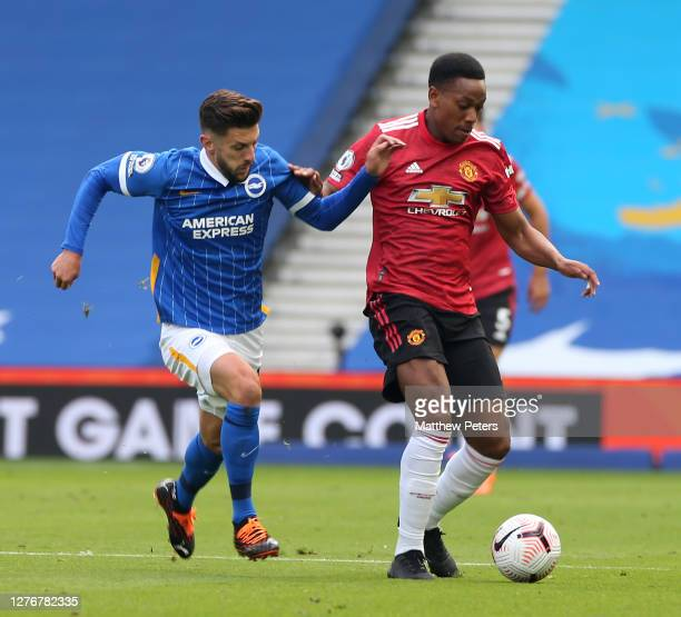 Anthony Martial of Manchester United in action with Adam Lallana of Brighton and Hove Albion during the Premier League match between Brighton Hove...