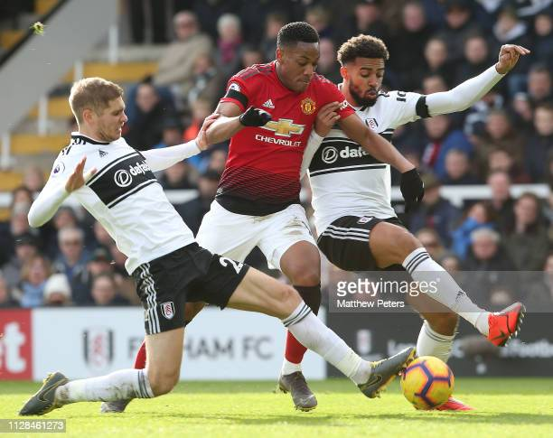 Anthony Martial of Manchester United in action with Maxime le Marchand and Cyrus Christie of Fulham FC during the Premier League match between Fulham...