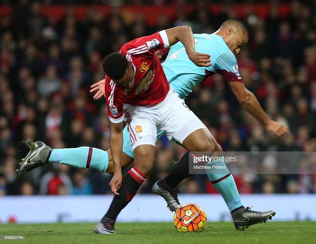 Anthony Martial of Manchester United in action with Winston Reid of West Ham United during the Barclays Premier League match between Manchester United and West Ham United at Old Trafford on December 05, 2015 in Manchester, England.