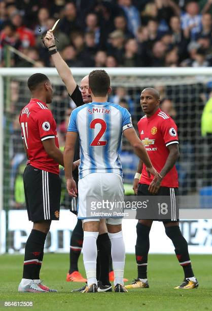 Anthony Martial of Manchester United is booked by referee Lee Mason during the Premier League match between Huddersfield Town and Manchester United...