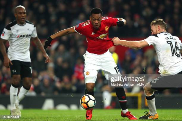 Anthony Martial of Manchester United is challenged by Alex Pearce of Derby County during the Emirates FA Cup Third Round match between Manchester...