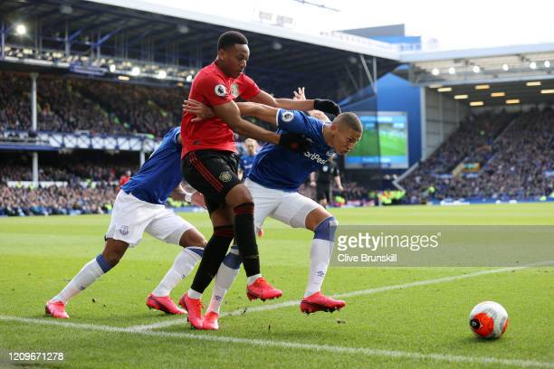 Anthony Martial of Manchester United is challenged by Djibril Sidibe and Richarlison of Everton during the Premier League match between Everton FC...