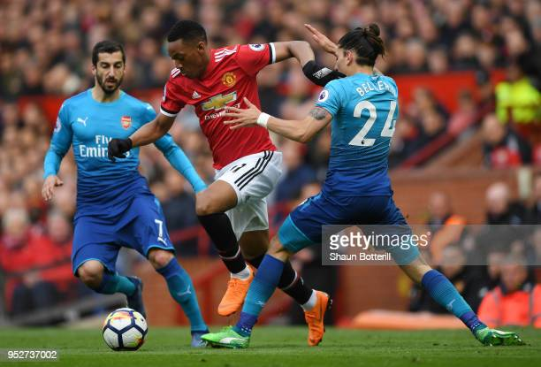 Anthony Martial of Manchester United is challenged by Hector Bellerin of Arsenal as Henrikh Mkhitaryan of Arsenal looks on during the Premier League...