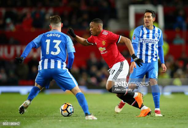 Anthony Martial of Manchester United is challenged by Pascal Gross of Brighton during the Emirates FA Cup Quarter Final between Manchester United and...