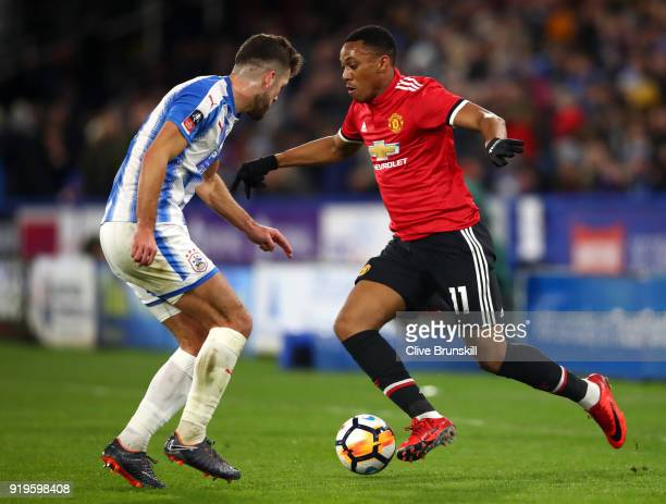 Anthony Martial of Manchester United is challenged by Tommy Smith of Huddersfield Town during the The Emirates FA Cup Fifth Round between...