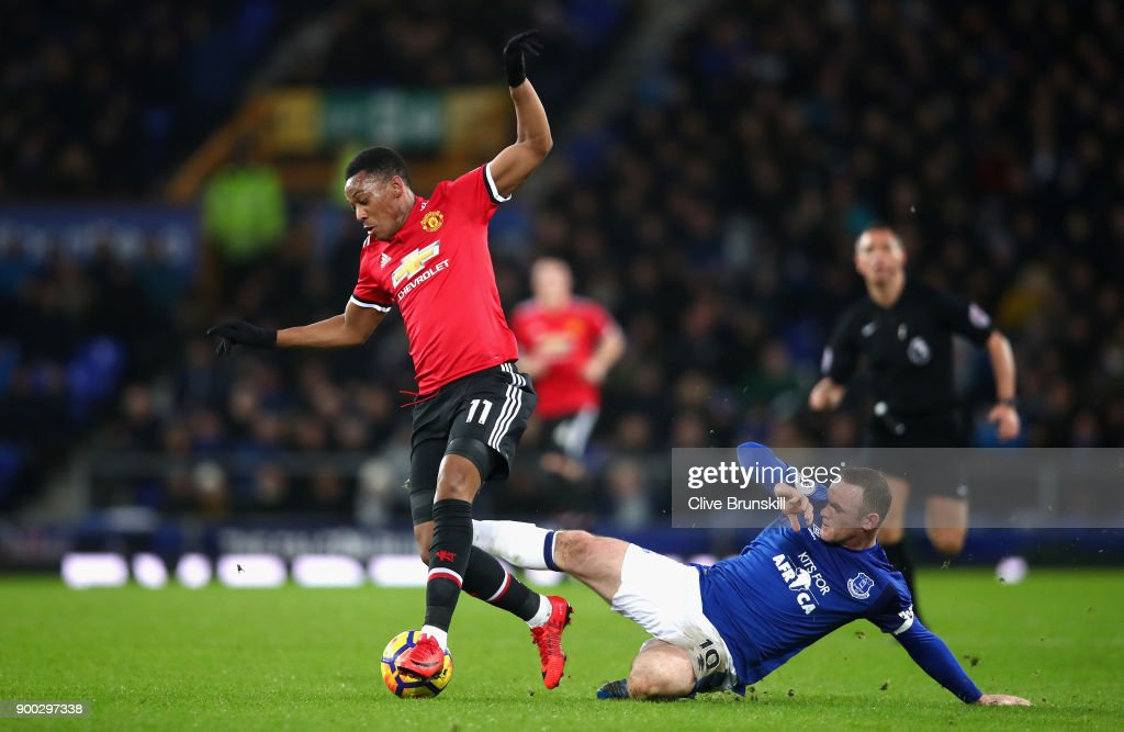 Anthony Martial of Manchester United is tackled by Wayne Rooney of Everton during the Premier League match between Everton and Manchester United at Goodison Park on January 1, 2018 in Liverpool, England.