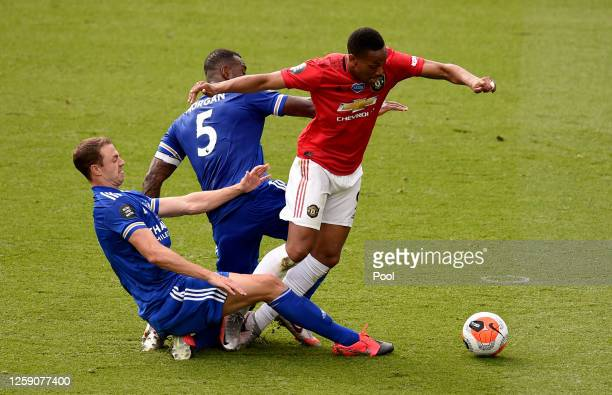 Anthony Martial of Manchester United is tackled by Wes Morgan and Jonny Evans both of Leicester City leading to a penalty during the Premier League...