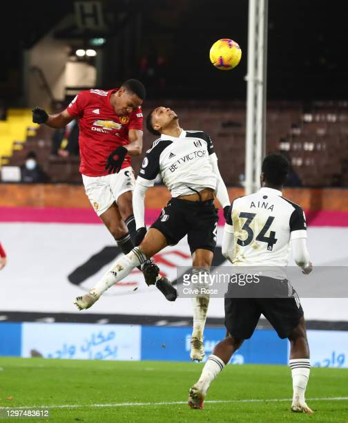 Anthony Martial of Manchester United jumps above Kenny Tete of Fulham to head towards goal during the Premier League match between Fulham and...
