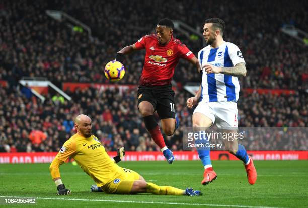 Anthony Martial of Manchester United jumps over David Button of Brighton and Hove Albion under pressure from Shane Duffy of Brighton and Hove Albion...