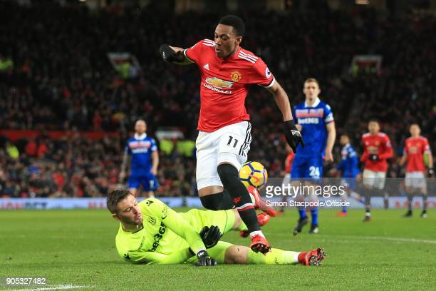 Anthony Martial of Manchester United jumps over Stoke City goalkeeper Jack Butland as he makes a save during the Premier League match between...