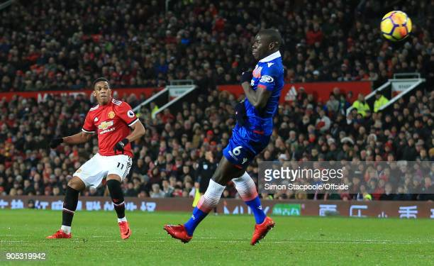 Anthony Martial of Manchester United puts the ball past Kurt Zouma of Stoke City to score their 2nd goal during the Premier League match between...