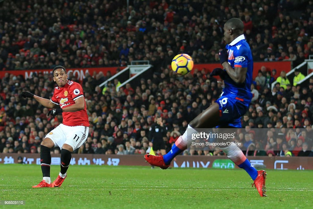 Anthony Martial of Manchester United puts the ball past Kurt Zouma of Stoke City to score their 2nd goal during the Premier League match between Manchester United and Stoke City at Old Trafford on January 15, 2018 in Manchester, England.