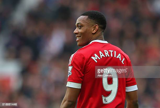 Anthony Martial of Manchester United smiles as he scores their first goal during the Barclays Premier League match between Manchester United and...