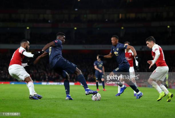Anthony Martial of Manchester United watches as Paul Pogba of Manchester United holds off Alexandre Lacazette of Arsenal during the FA Cup Fourth...