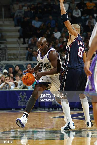 Anthony Mason of the Milwaukee Bucks drives past Kenyon Martin of the New Jersey Nets during the NBA game at the Bradley Center on November 6 2002 in...
