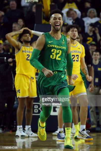 Anthony Mathis of the Oregon Ducks celebrates a 71-70 overtime win in front of Isaiah Livers and Brandon Johns Jr. #23 of the Michigan Wolverines at...