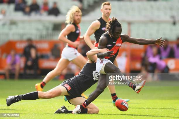 Anthony McDonaldTipungwuti of the Bombers kicks whilst being tackled by Matthew Kreuzer of the Blues during the round eight AFL match between the...