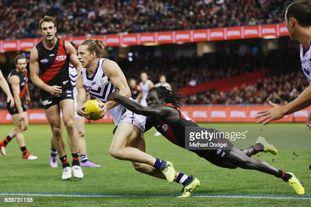 Anthony McDonaldTipungwuti of the Bombers tackles Nat Fyfe of the Dockers during the round 23 AFL match between the Essendon Bombers and the...