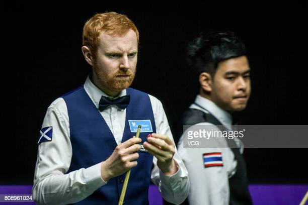 Anthony McGill of Scotland chalks the cue against Thepchaiya UnNooh of Thailand and Noppon Saengkham of Thailand on day one of 2017 Snooker World Cup...