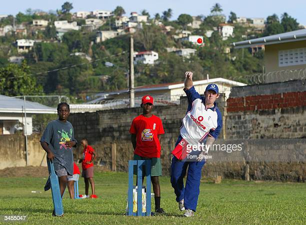 Anthony McGrath of England plays cricket with the kids during a visit to the local orphanage on April 21 2004 in Port of Spain Trinidad