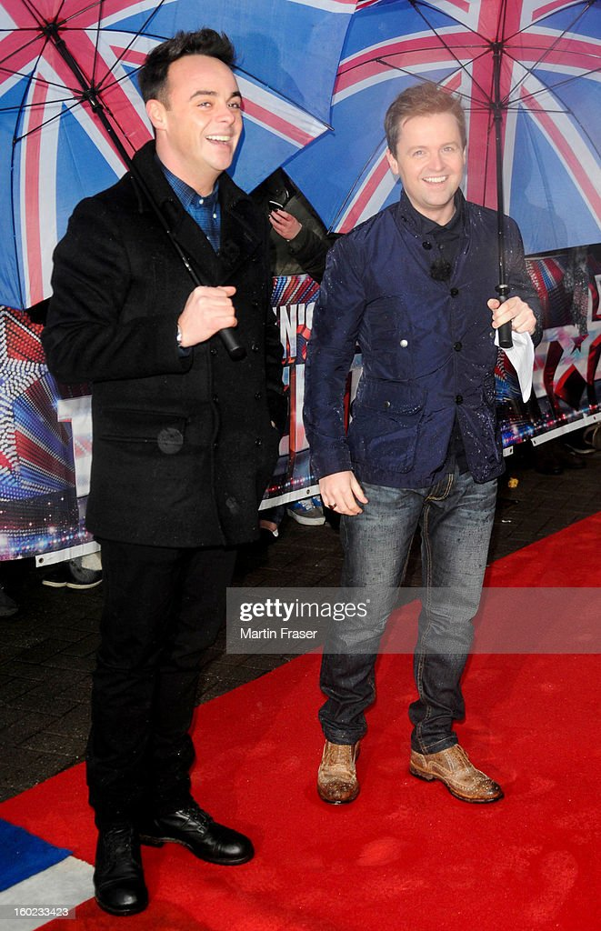 Anthony McPartlin (L) and Declan Donnelly arrive under Union Jack umbrellas at the very wet Glasgow auditions for Britain's Got Talent, at Clyde Theatre on January 28, 2013 in Glasgow, Scotland.