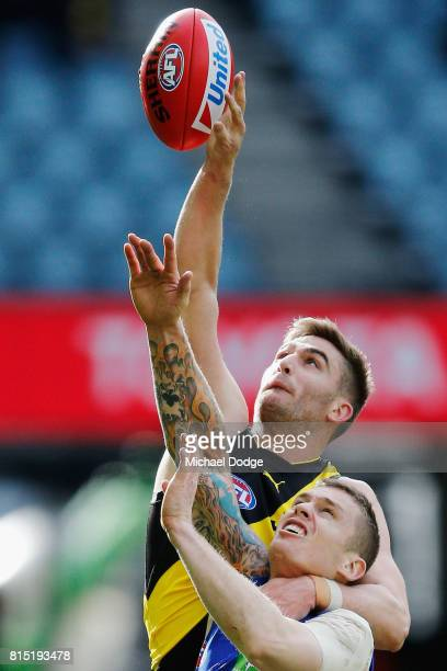 Anthony Miles of the Tigers compete for the ball over Dayne Beams of the Lions during the round 17 AFL match between the Richmond Tigers and the...