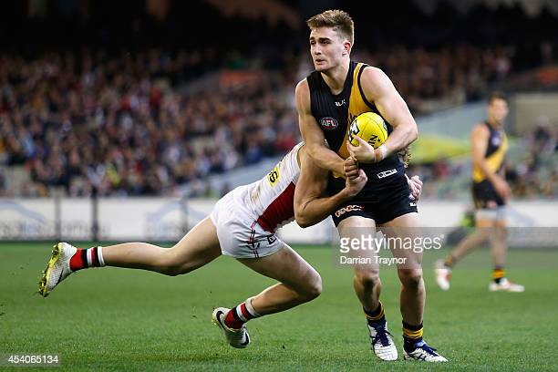 Anthony Miles of the Tigers is tackled during the round 22 AFL match between the Richmond Tigers and the St Kilda Saints at Melbourne Cricket Ground...