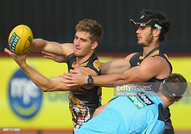 Anthony Miles of the Tigers passes the ball during the Richmond Tigers AFL training session at ME Bank Centre on March 19 2015 in Melbourne Australia