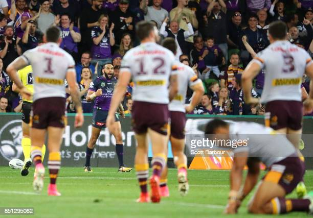 Anthony Milford and the Broncos look dejected as Josh AddoCarr of the Storm celebrates after running away to score the first try during the NRL...